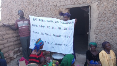 Issa Yalcouyé standing and holding the banner of thanks from the center in Danaguiri