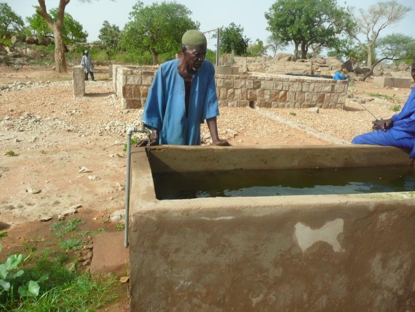 PÇbälou TEMBINE observe attentivement le remplissage du bassin avant l'arrivÇ des autres vieux pour le partage.